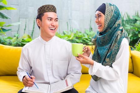 femmes muslim: Musulman asiatique et femme de boire du caf� ou du th� dans le salon en costume traditionnel