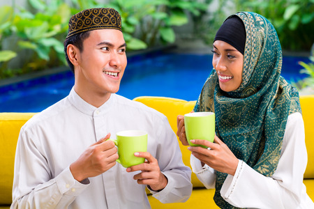 Asian Muslim man and woman drinking coffee or tea in living room wearing traditional dress photo