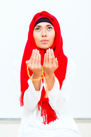 hand chain: Asian Muslim woman praying with beads chain wearing traditional dress