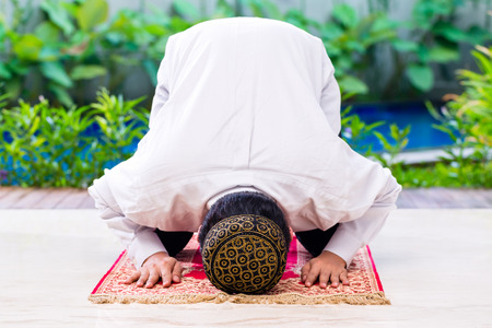 muslim: Asian Muslim man praying on carpet wearing traditional dress