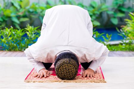 Hombre musulmán asiática que ruega en la alfombra con un vestido tradicional Foto de archivo