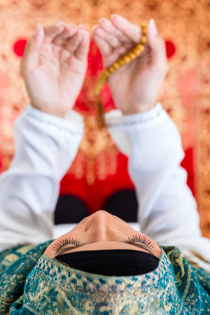 Asian Muslim woman praying on carpet with beads chain wearing traditional dress Stock Photo