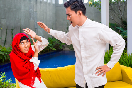 forcing: Asian Muslim man forcing and smack woman with hand in living room wearing traditional dress