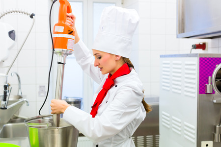 food processor: Female Chef preparing ice cream with food processor in gastronomy parlor kitchen