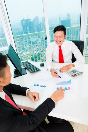 bank manager: Asian banker offering client finance assets in bank office