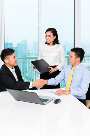 insurance consultant: Asian banker counseling client finance investment in bank office