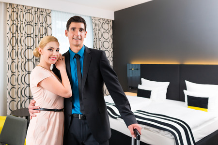 Man and woman arrive in hotel room photo