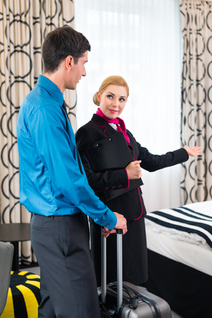 Hotel manager or receptionist welcoming man and showing room photo