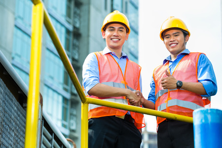 safety check: Asian Indonesian construction workers with blueprint or plan on building site Stock Photo