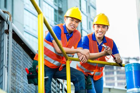 アジアの建築敷地のヘルメット、安全ベストとアジアのインドネシアの建設労働者