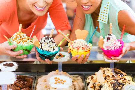 若い女性客またはコルネットとコーンとパーラーのサンデーのアイスクリームの種類を持つ友人