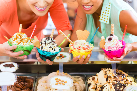 Young female customers or friends with sorts of ice cream for cornets and cones and sundaes in parlor
