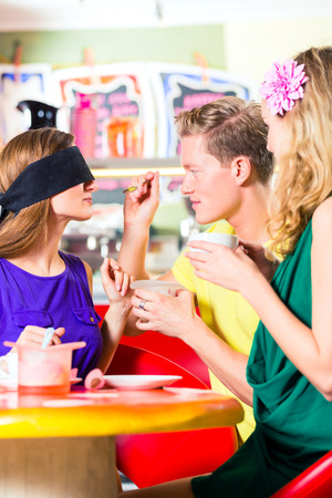 guessing: Friends tasting ice-cream with bond eyes, guessing taste in ice cream parlor or cafe Stock Photo