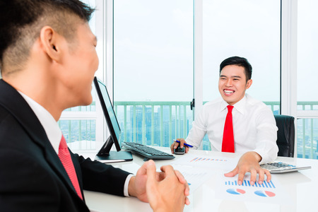 Asian banker offering client finance assets in bank office photo