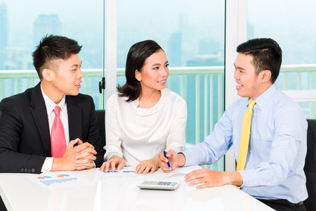 Asian banker selling insurance to couple photo