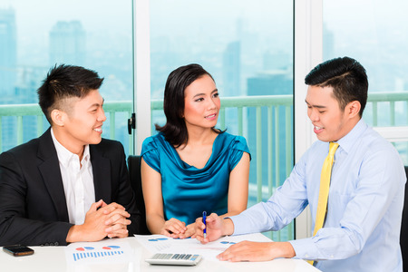 Asian banker selling insurance to couple