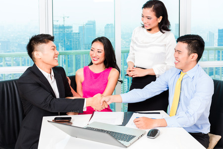 financial consultants: Asian banker team counseling client finance investment in bank office