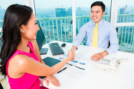 Asian advisor with client on financial investment photo