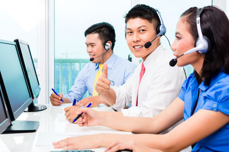 telemarketer: Asian Chinese call center agent team on phone Stock Photo