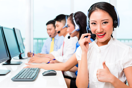 asian office lady: Asian Chinese call center agent team on phone Stock Photo