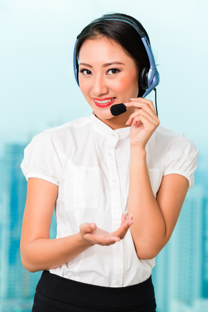 costumer: Asian woman working in call center wearing headset Stock Photo