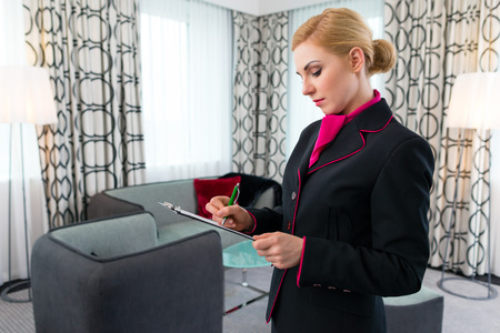Housekeeping manager or assistant controlling hotel suit or suit with checklist on tidiness Stock Photo