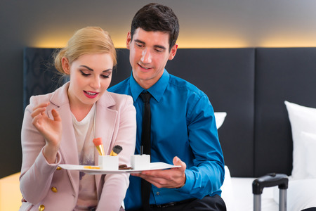 Man and woman eating at arrival in hotel room sweet dessert photo