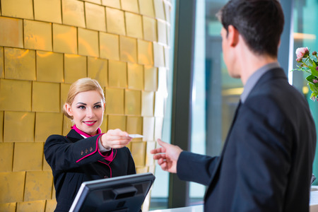 business reception: Man in Hotel check in at reception or front office being given key card Stock Photo