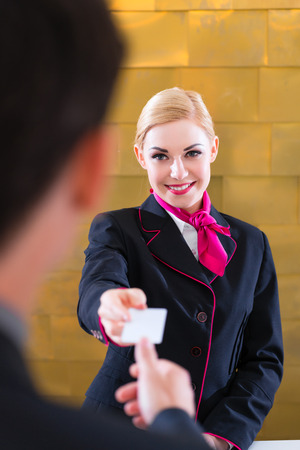 front office: Man in Hotel check in at reception or front office being given key card Stock Photo