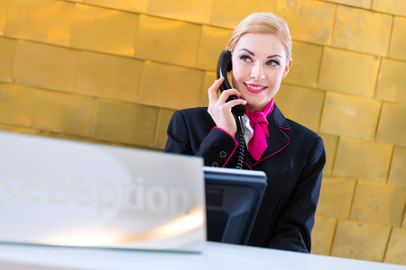front desk: Hotel receptionist with phone on front desk Stock Photo