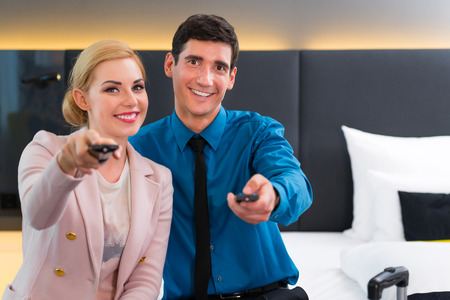switching: Couple switching TV with remote control in hotel room