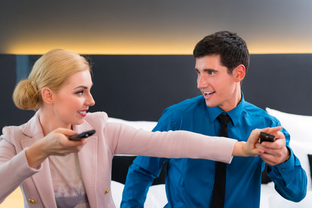 Couple switching TV with remote control in hotel room photo