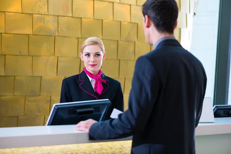uniformes de oficina: Hombre en hotel Fecha de entrada en la recepción o en la oficina frontal está dando la tarjeta llave Foto de archivo