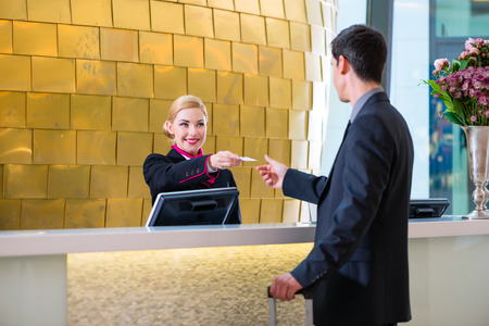 Man in Hotel check in at reception or front office being given key card Foto de archivo