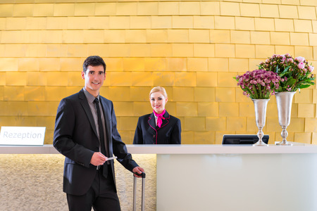 Man in Hotel check in at reception or front office being given key card Stock Photo