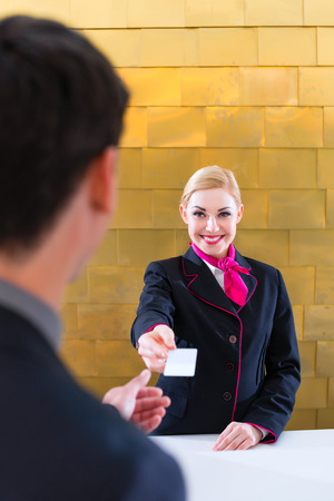 check in: Man in Hotel check in at reception or front office being given key card Stock Photo