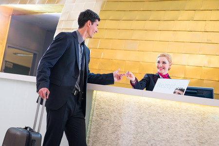 front of: Man in Hotel check in at reception or front office being given key card Stock Photo