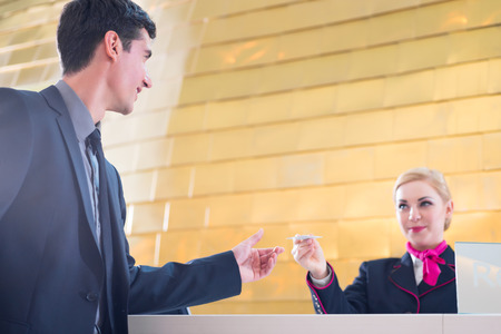 attend: Man in Hotel check in at reception or front office being given key card Stock Photo
