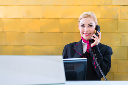 Hotel receptionist with phone on front desk Stock Photo