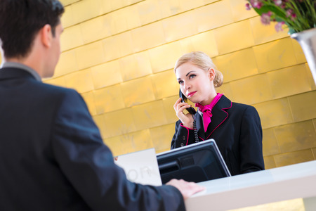 front desk: Hotel receptionist telephoning with guest for reservation or information Stock Photo