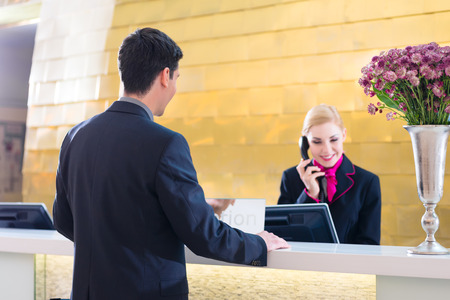 concierge: Hotel receptionist telephoning with guest for reservation or information Stock Photo