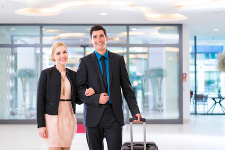 arriving: Man and woman arriving at hotel lobby with suitcase Stock Photo