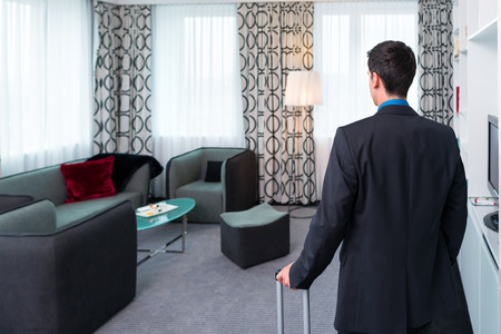 arriving: Man at arriving in hotel room Stock Photo