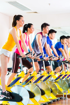 spin: Chinese Asian sport group of men and women in fitness club or gym exercising on spinning bikes