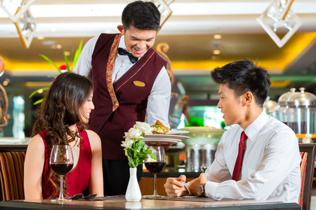 waiter serving: Asian Chinese couple - Man and woman - or lovers having a date or romantic dinner in a fancy restaurant while the waiter is serving food