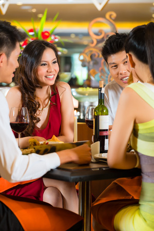 clique: Four Asian Chinese business people having dinner in elegant club restaurant or hotel Stock Photo