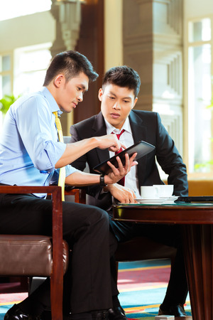 office lobby: Two Asian Chinese businessman or office people having a business meeting in a hotel lobby discussing documents on a tablet computer while drinking coffee Stock Photo