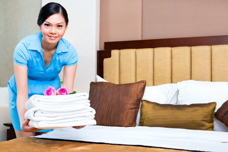 room service: Chambermaid cleaning in Asian hotel room