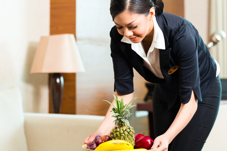 Asian Chinese hotel executive housekeeper placing fruit treatment to welcome arriving VIP guests Stock Photo