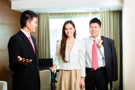 arriving: Asian Chinese Hotel Manager or director or supervisor presenting arriving VIP guests the room or suite